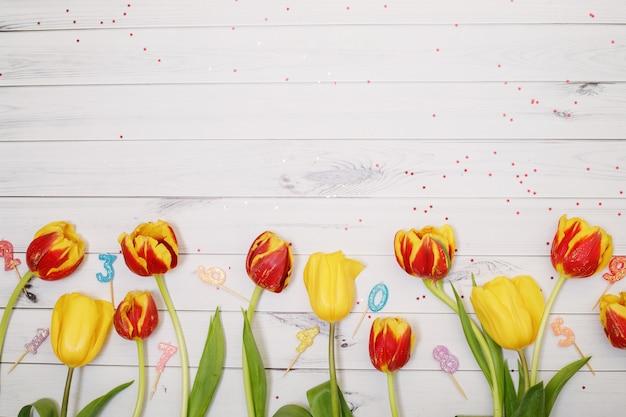 Rote, gelbe tulpen blüht, kerze und konfetti im hölzernen hintergrund. Premium Fotos