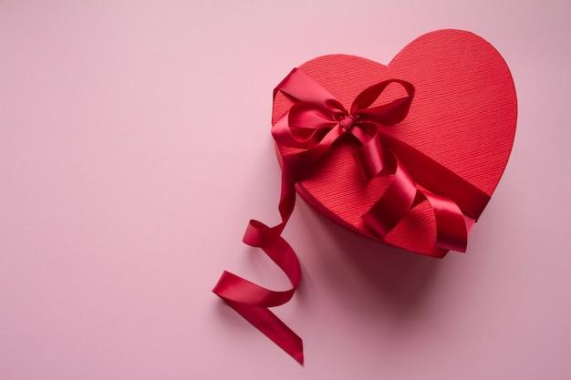 Rote geschenkboxherzform mit rotem band Premium Fotos