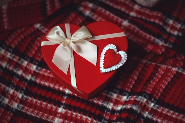 Rote geschenkschachtel in herzform mit weißer schleife und herzförmiger verzierung aus filz Premium Fotos