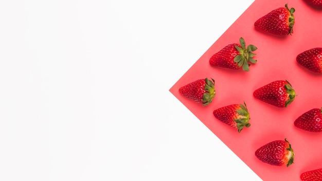 Rote geschmackvolle erdbeeren auf rosafarbenem und weißem mehrfarbigem hintergrund Kostenlose Fotos