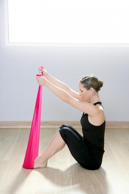 Rote gummi-turnhallenfrau des pilates-yoga-widerstandsband Premium Fotos