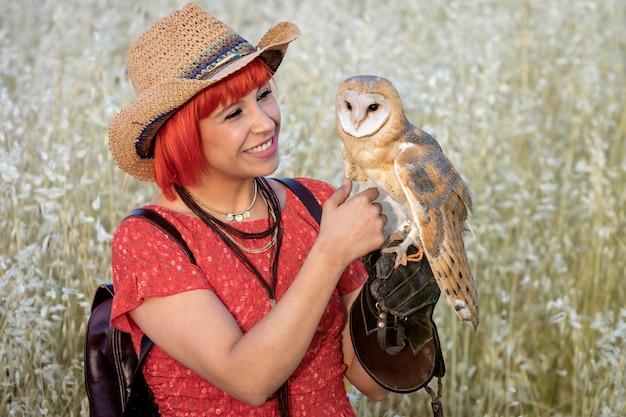 Rote haarfrau mit einer weißen eule auf ihrem arm Premium Fotos