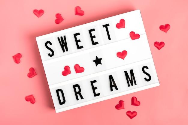 Rote herzen, lightbox mit zitat süße träume auf rosa hintergrund flache lage Premium Fotos