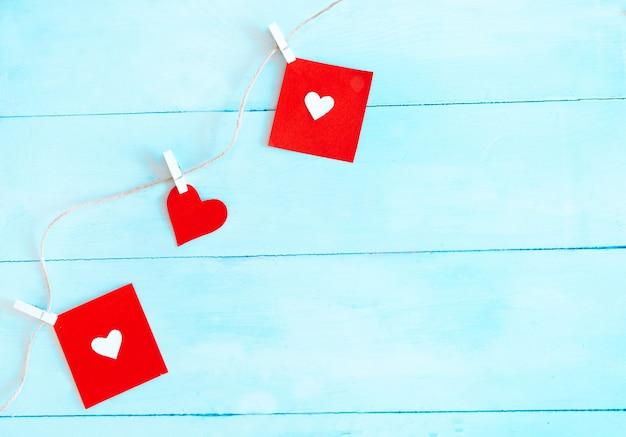 Rote herzen stellten auf schnur über blauem hintergrund ein. valentinstag-konzept. Premium Fotos