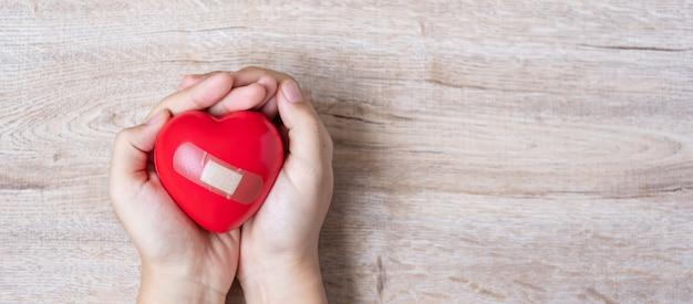 Rote herzform auf hölzernem hintergrund halten. gesundheitswesen Premium Fotos