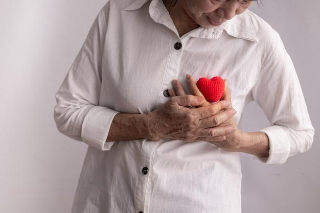 Rote herzform des asiatischen älteren frauengriffs, konzept der herzkrankheit. Premium Fotos