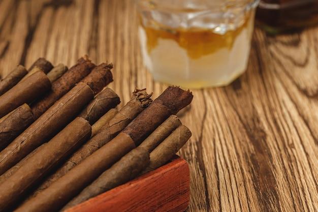 Rote holzkiste mit neuen gerollten zigarren auf holztisch Premium Fotos