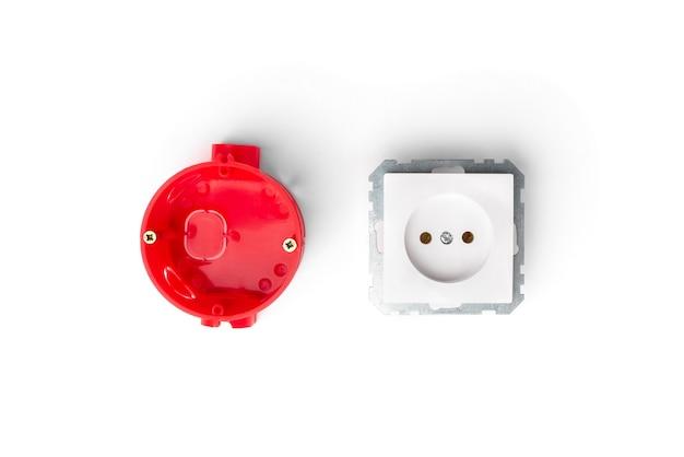 Rote installation elektrokasten für steckdosen und weiße steckdose und drähte auf betonhintergrund. Premium Fotos