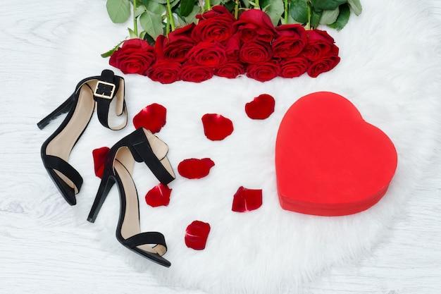 Rote kästchen in herzform, schwarze schuhe und ein strauß roter rosen auf weißem fell Premium Fotos