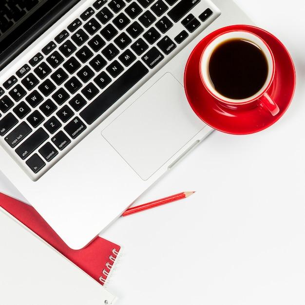 Rote kaffeetasse auf einem offenen laptop über weißem hintergrund Kostenlose Fotos