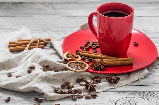 Rote kaffeetasse auf einem teller, hölzerner hintergrund, getränk, weihnachtsmorgen Kostenlose Fotos
