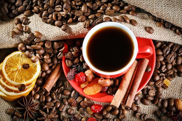 Rote keramische schale mit heißem kaffee auf hölzernen brettern. Premium Fotos