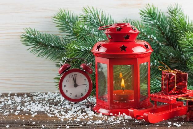 Rote kerzenlaterne der weihnacht, weihnachtsbaum und dekorationen auf weißem hölzernem hintergrund. Premium Fotos