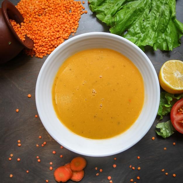 Rote linsensuppe in einer schüssel mit karotte, salatblatt, zitrone, tomate, rohen linsen Kostenlose Fotos