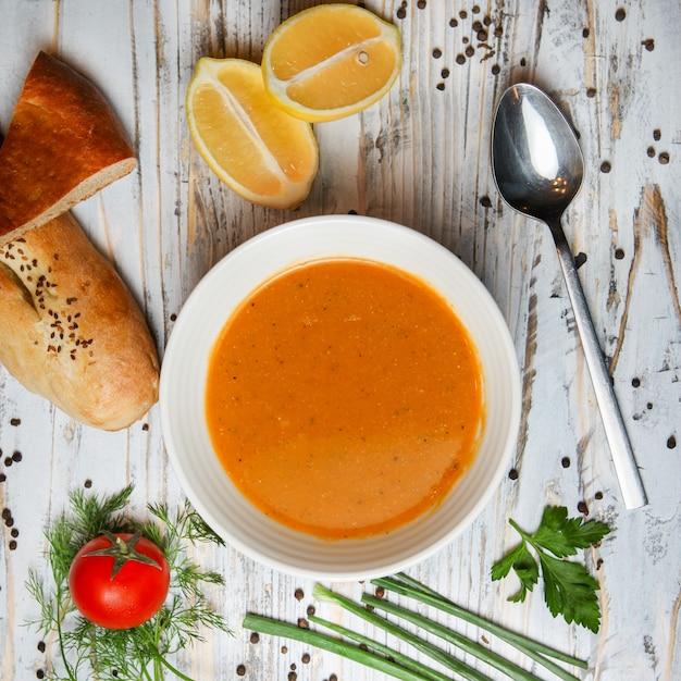 Rote linsensuppe mit zitrone, tomate, brot, kräutern, gewürzen, löffel in einer schüssel Kostenlose Fotos