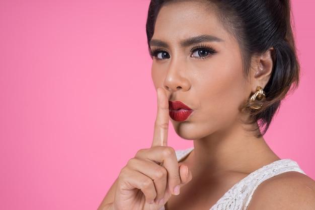 Rote lippen und finger der asiatischen frau der schönheit, die stillezeichen zeigt Kostenlose Fotos