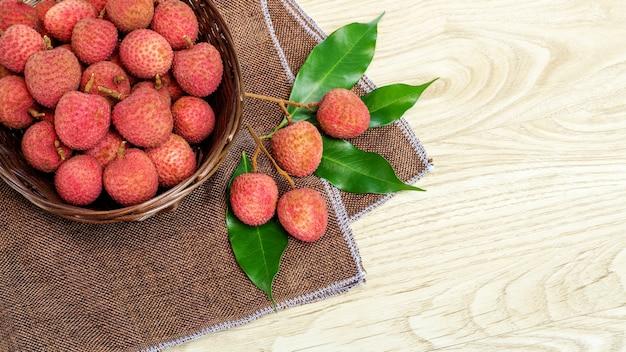 Rote litschifrucht auf einem holztisch. Premium Fotos