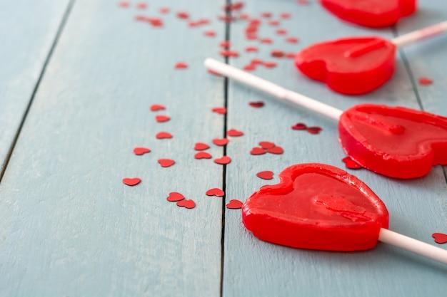 Rote lutscher mit herzform auf blauer holzoberfläche lieben konzept valentinstag. Premium Fotos
