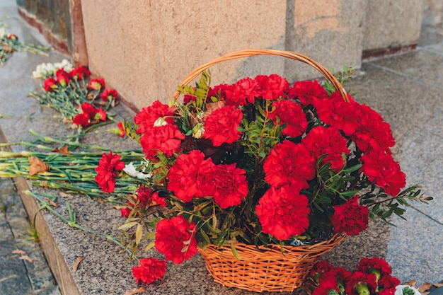 Rote nelken in der nähe des denkmals als symbol der erinnerung. Premium Fotos