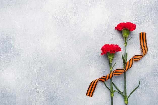 Rote nelken und st. george ribbon auf einem konkreten hintergrund. Premium Fotos