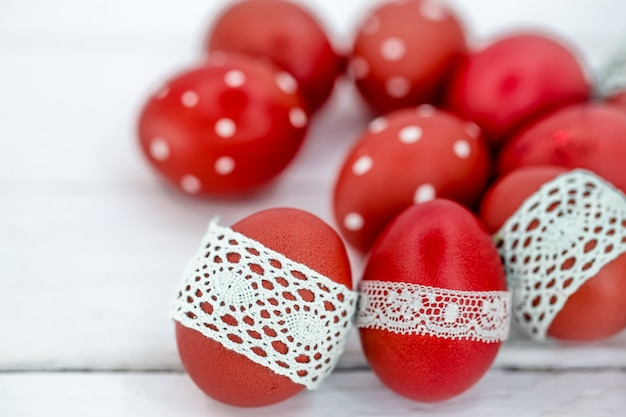 Rote ostereier auf weißem gebundenem spitzenband, nahaufnahme, liegend auf einem weißen holz Kostenlose Fotos