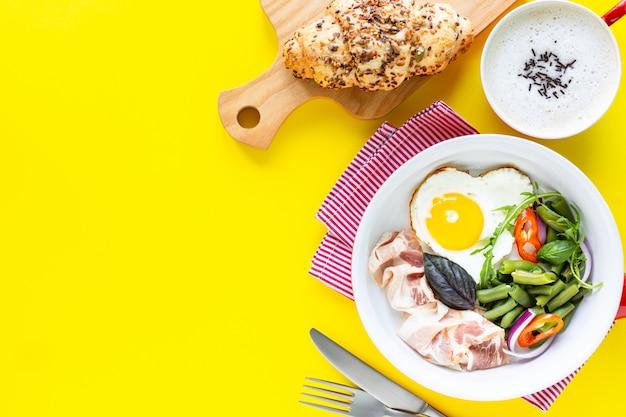 Rote pfanne mit köstlichem frühstück auf einem gelben, kopierraum. draufsicht, selektiver fokus. Kostenlose Fotos