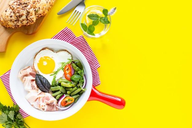 Rote pfanne mit köstlichem frühstück auf gelbem hintergrund, kopienraum. draufsicht, selektiver fokus. Kostenlose Fotos