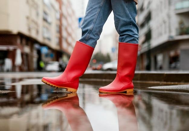 Rote regenstiefel auf der straße Kostenlose Fotos