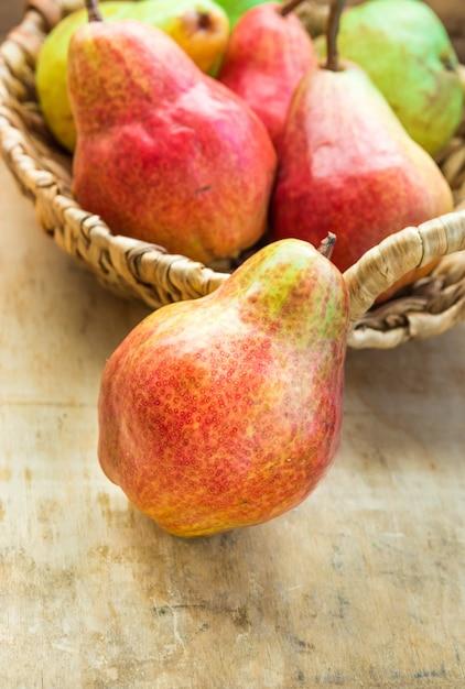 Rote reife organische birnen im weidenkorb auf gealterter hölzerner tabelle Premium Fotos