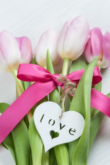 Rote rosa tulpen mit rotem band Premium Fotos