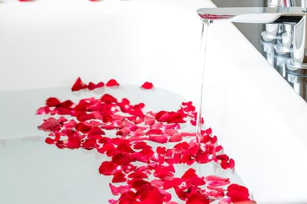 Rote rosafarbene Blumenblätter in der Badewanne am ...