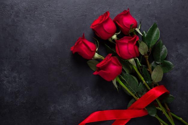 Rote rose blüht blumenstrauß auf schwarzem stein. Premium Fotos
