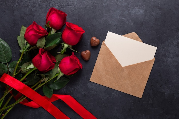 Rote rose blüht blumenstrauß, umschlag, schokoladenbonbons auf schwarzem stein. valentinstag-grußkarte Premium Fotos