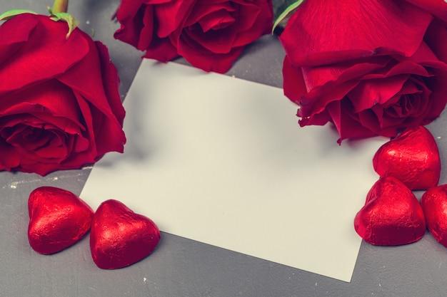 Rote rose und leere geschenkkarte für text Premium Fotos