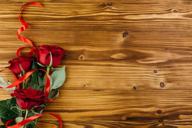 Rote rosen mit band auf tabelle Kostenlose Fotos