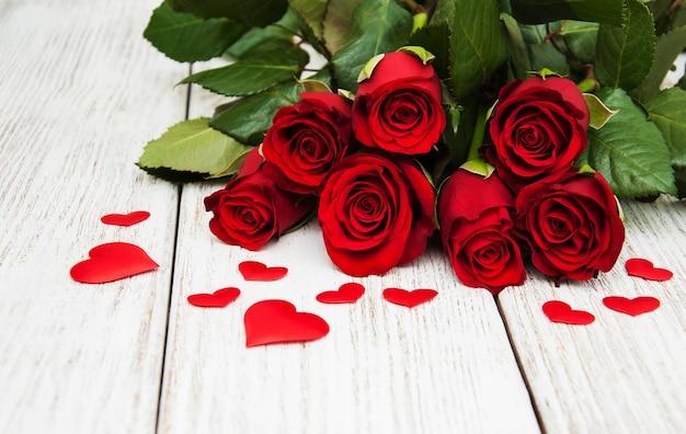 Rote rosen mit seidenherzen Premium Fotos