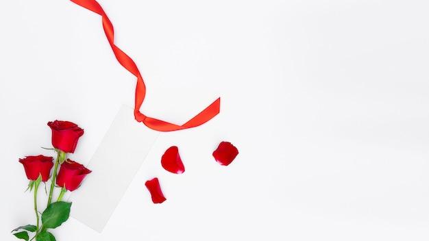 Rote rosen, silberner rohling mit rotem band und blütenblättern isoliert Premium Fotos