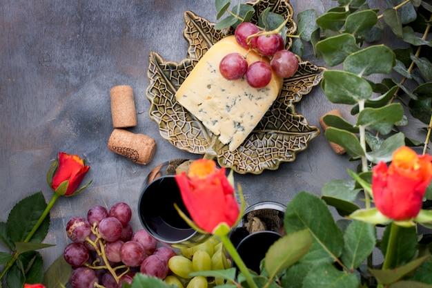 Rote rosen, trauben, käse und ein glas rotwein auf einem grauen konkreten hintergrund Premium Fotos