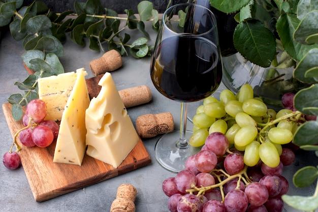 Rote rosen, trauben, käse und ein glas rotwein auf einem schwarzen konkreten hintergrund Premium Fotos