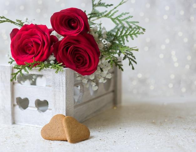 Rote rosen und herzen mit einem glänzenden hintergrund Premium Fotos