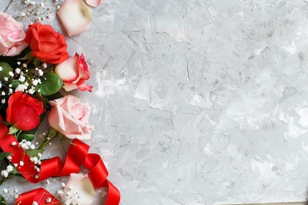 Rote rosen und kleine weiße blumen mit band auf grauem hintergrund Premium Fotos