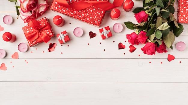 Rote rosen und valentinstagdekorationen draufsicht auf weißem hölzernem hintergrund Premium Fotos