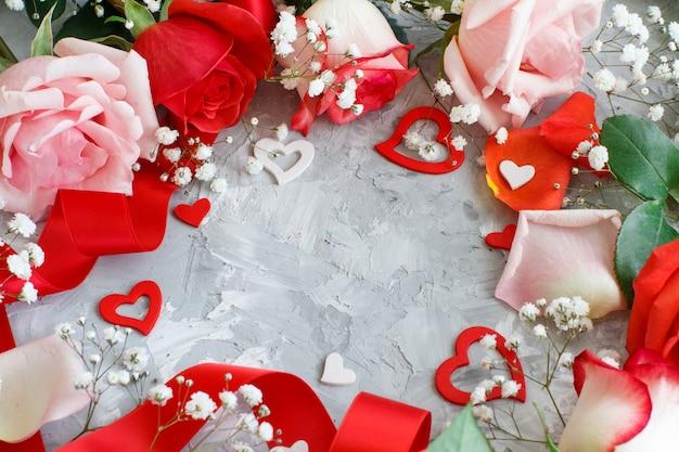 Rote rosenblumen, blütenblätter und herzen auf grauem hintergrund Premium Fotos