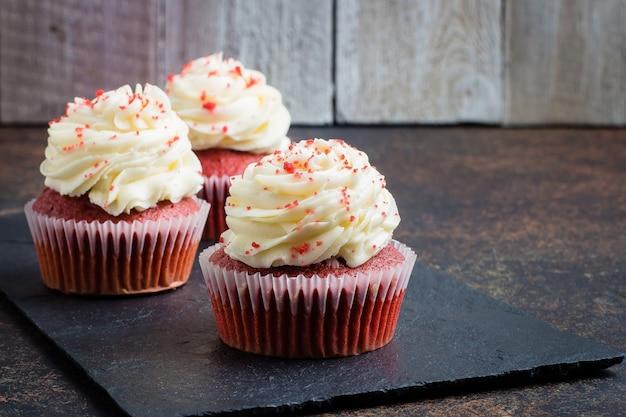 Rote samtkleine kuchen auf schieferbrett auf dunklem steintabellenhintergrund. dessert für den urlaub Premium Fotos
