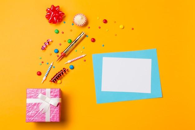 Rote schleife; aalaw; edelsteine; luftschlangen und streusel mit grußkarte und rosa kasten auf gelbem hintergrund Kostenlose Fotos
