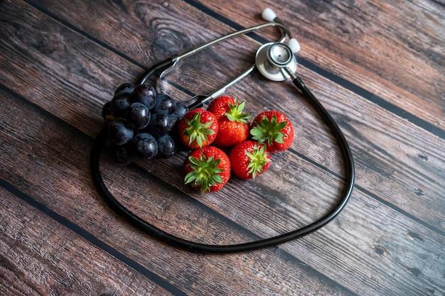 Rote schottische erdbeeren und schwarze trauben mit stethoskop auf holztisch Kostenlose Fotos