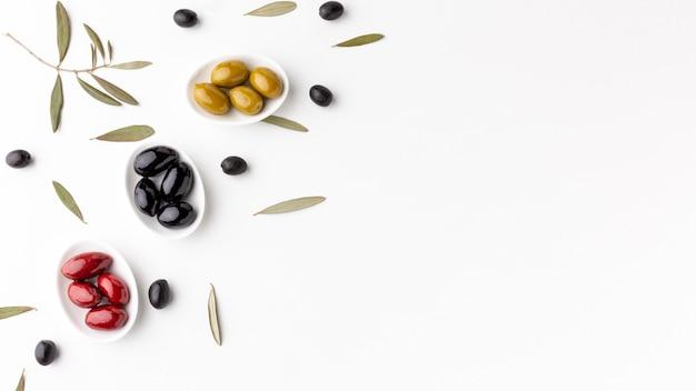 Rote schwarze gelbe oliven auf platten mit kopienraum Kostenlose Fotos