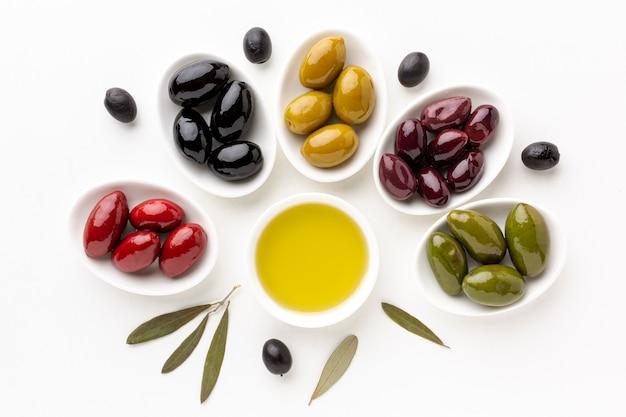 Rote schwarze gelbe purpurrote oliven auf platten mit blättern und olivenuntertasse Kostenlose Fotos