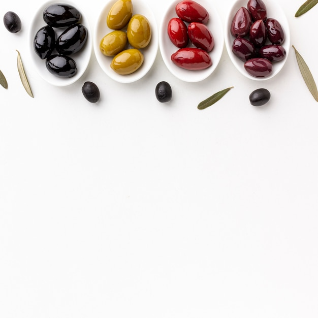 Rote schwarze gelbe purpurrote oliven auf platten mit kopienraum Kostenlose Fotos