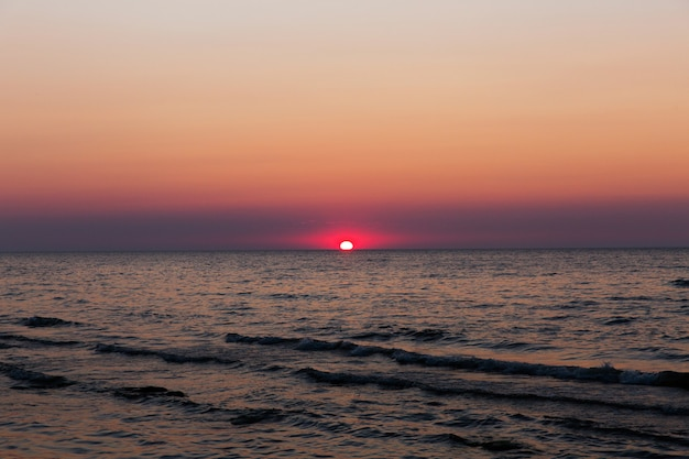 Rote sonne bei sonnenuntergang. sonnenuntergang am meer. schöne abendlandschaft. wellen in einem meer bei sonnenuntergang Premium Fotos